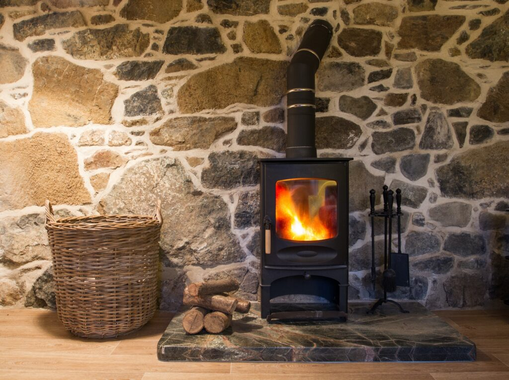 A wood burning stove fireplace in a cosy stone cottage with copy space